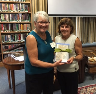 Lori Scudder, President, with winner of a set of Gil's books Mary  Simonetti
